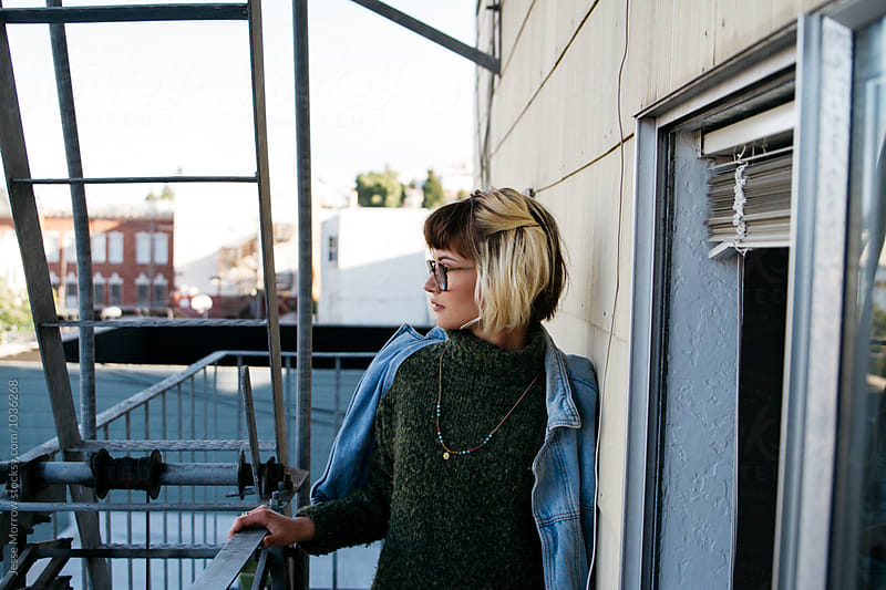 Portrait of young female woman girl on fire escape in urban city environment by Jesse Morrow for Stocksy United