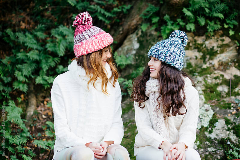 Mother and daughter wearing wool cap and scarf sitting on a bench and talking in Winter by Beatrix Boros for Stocksy United