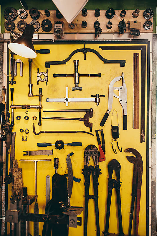 Tools and sprockets organized on a yellow wall by Lior + Lone for Stocksy United