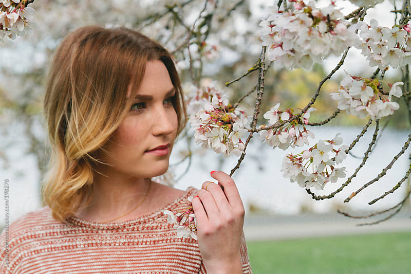 Young woman under cherry blossom by Jesse Morrow for Stocksy United