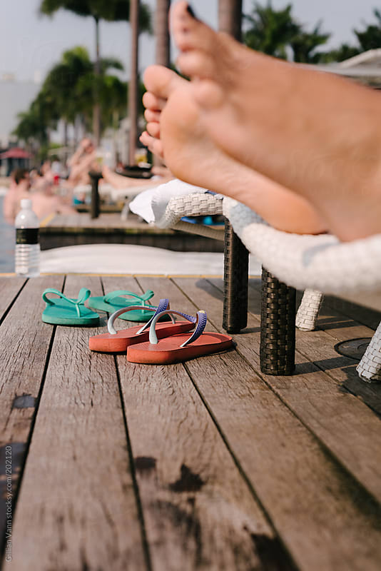 shoes off, relaxing in the sun by the pool by Gillian Vann for Stocksy United