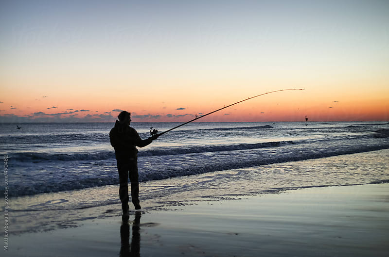 Silhouette of person surf fishing alone on ocean beach with long rod at sunset by Matthew Spaulding for Stocksy United