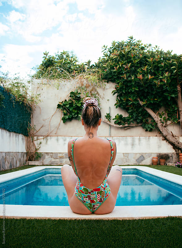 Young woman in the pool, turning her back at the camera by Susana Ramírez for Stocksy United