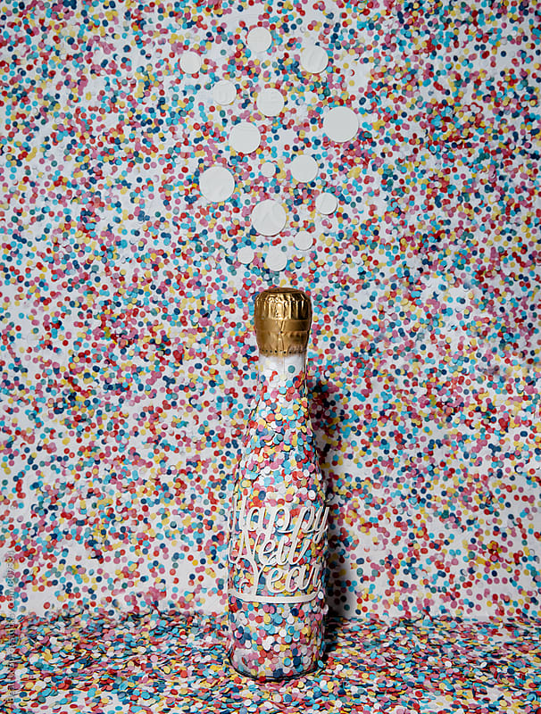 Bubbles above a champagne bottle with confetti everywhere by Beatrix Boros for Stocksy United