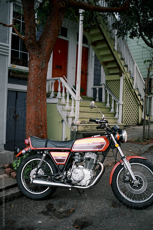 Old small 350 motorcycle sitting on an urban city street. by Lucas Saugen for Stocksy United