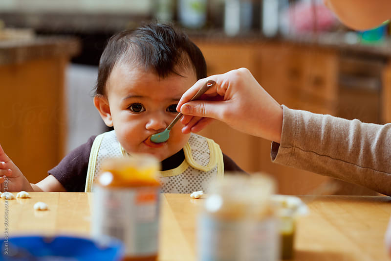 Baby: Mother Feeds Baby Variety Of Foods by Sean Locke for Stocksy United