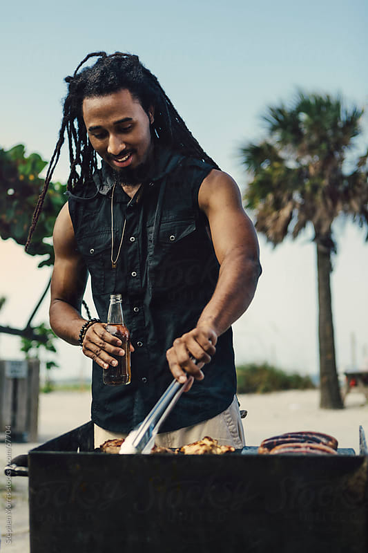 Man Grilling Steak at the Beach by Stephen Morris for Stocksy United
