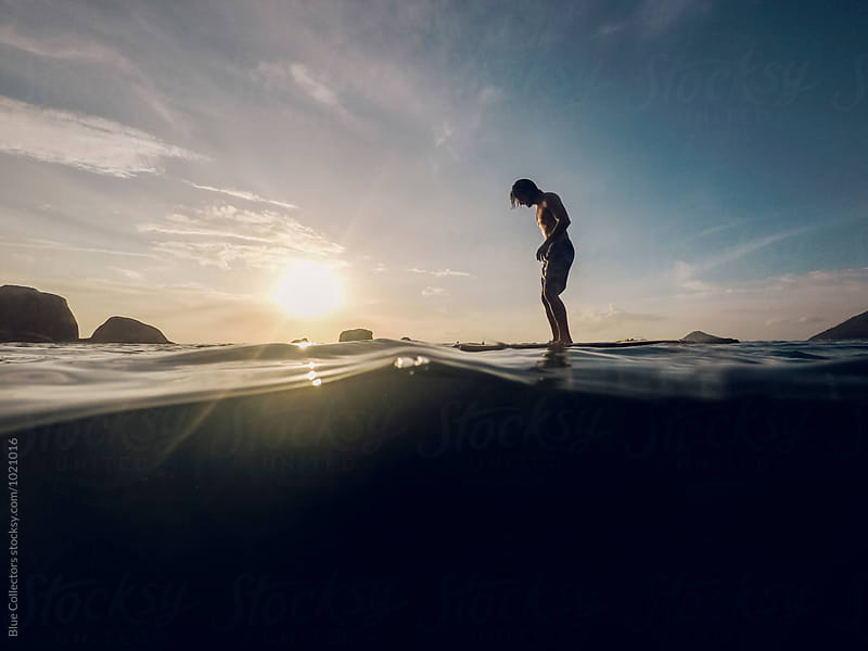 Young sport man be standing over the floating platform of bamboo in the sea sunset by Blue Collectors for Stocksy United