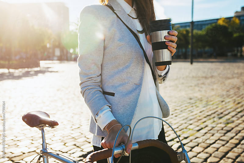 Closeup of a businesswoman standing with her bike and holding a coffee outside. by BONNINSTUDIO for Stocksy United