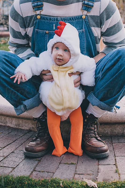 Dad Holding Baby in Chicken Costume by Gabrielle Lutze for Stocksy United