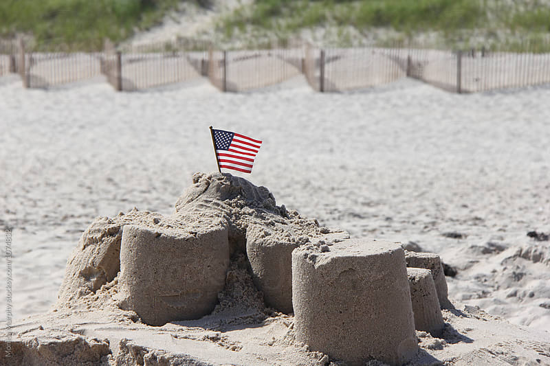 American Flag in a sand castle on the beach by Monica Murphy for Stocksy United