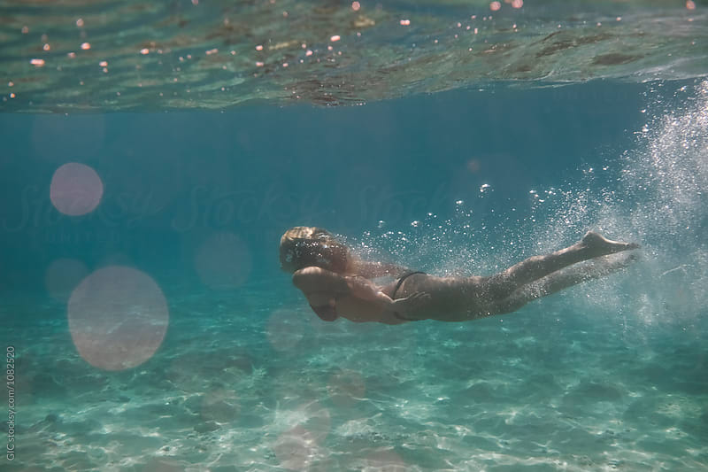 Young woman underwater by Simone Becchetti for Stocksy United