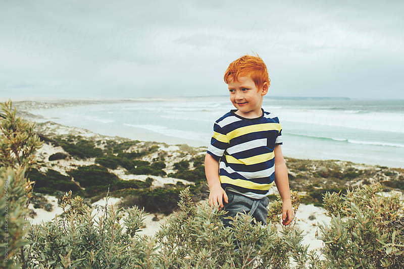Young boy at the beach by Robert Lang for Stocksy United