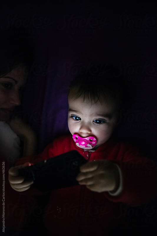 Baby using a mobile phone lying down on a bed next to her mother by Alejandro Moreno de Carlos for Stocksy United