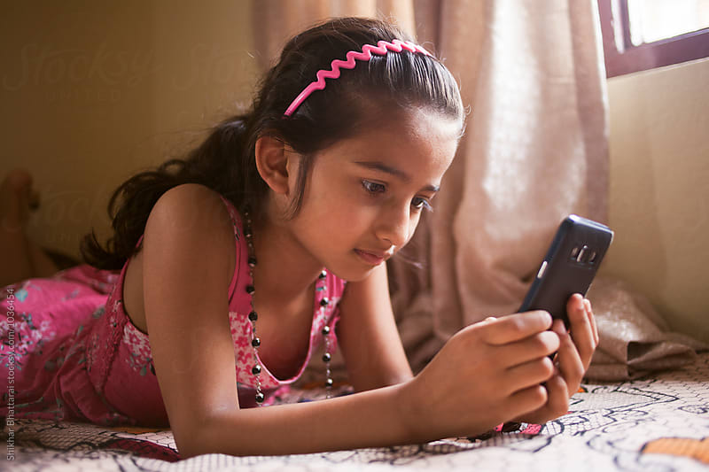 Young south asian girl on a mobile phone. by Shikhar Bhattarai for Stocksy United