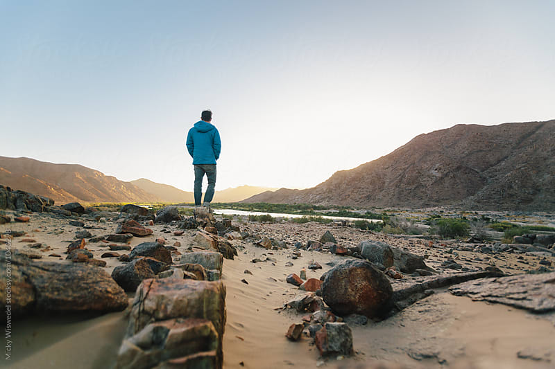 Hiker in a desert landscape at sunset by Micky Wiswedel for Stocksy United