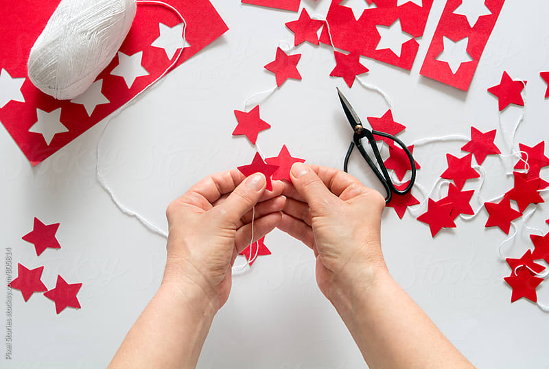 Woman making diy red stars Christmas garland by Pixel Stories for Stocksy United