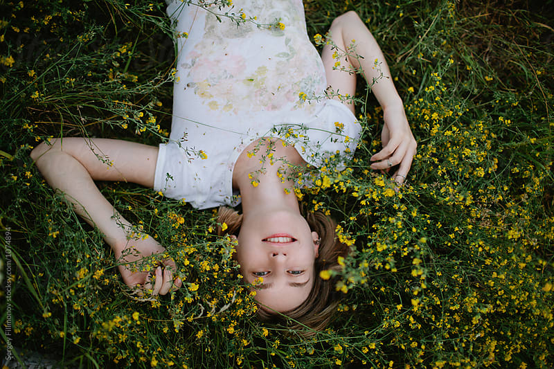 Charming woman lying in field flowers  by Sergey Filimonov for Stocksy United