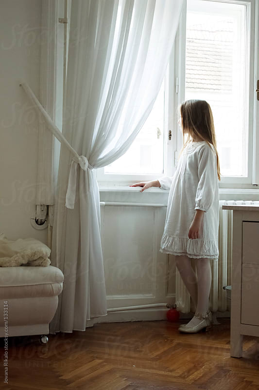Little girl watching trough the window in her lovely room by Jovana Rikalo for Stocksy United