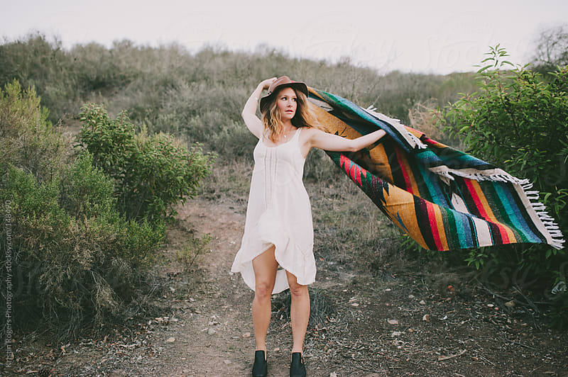 Pretty stylish woman playing with blanket in nature by Kristin Rogers Photography for Stocksy United