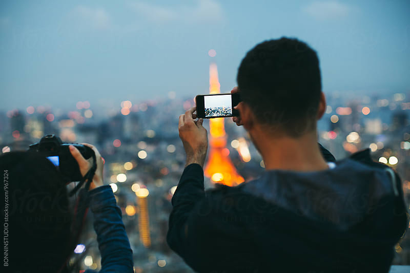 Back view of a man taking photo with his phone of Tokyo tower. by BONNINSTUDIO for Stocksy United