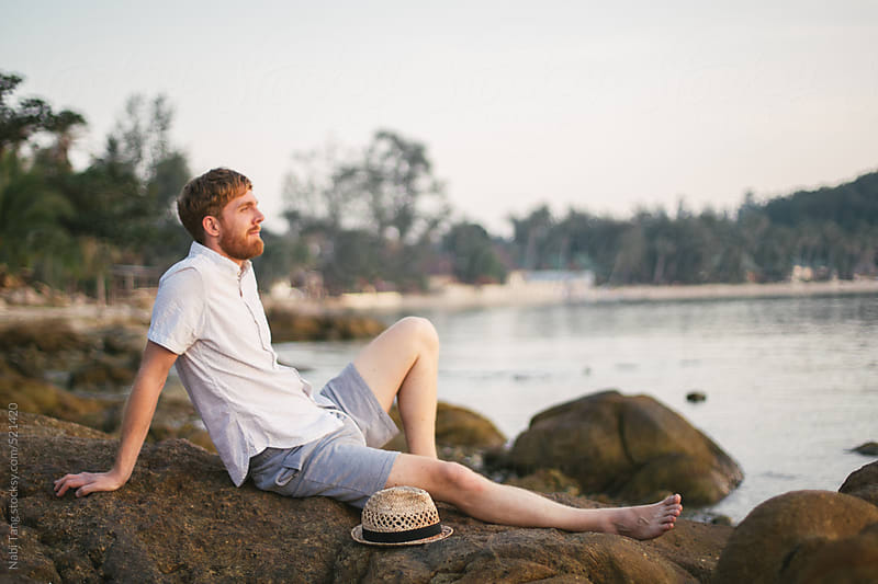 Handsome hipster man sitting on the rock enjoy the sunset on the island by Nabi Tang for Stocksy United