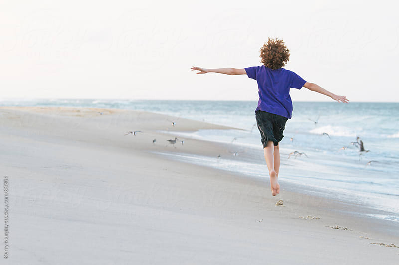Young white boy with red curly hair running on beach by Kerry Murphy for Stocksy United