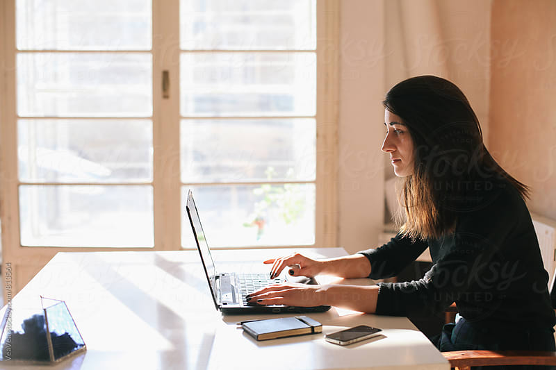 Brunette woman working on a laptop in her home office  by VeaVea for Stocksy United