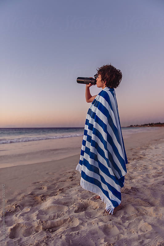 Boy wrapped in a towel having a drink from a bottle at the beach at sunset by Angela Lumsden for Stocksy United
