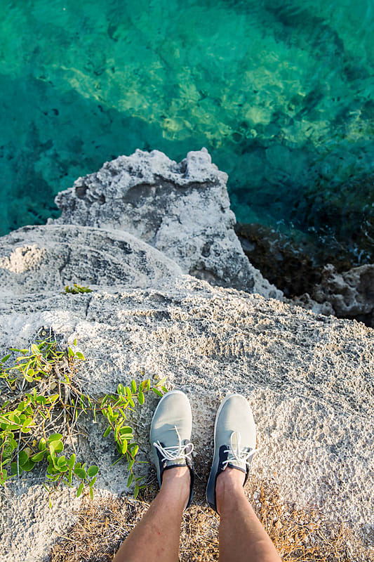 Feet of a man looking down from a cliff into the ocean water by Jovo Jovanovic for Stocksy United