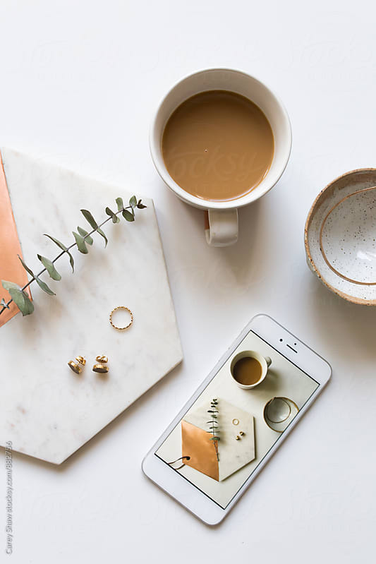 Modern desktop with coffee, phone, and jewelry by Carey Shaw for Stocksy United