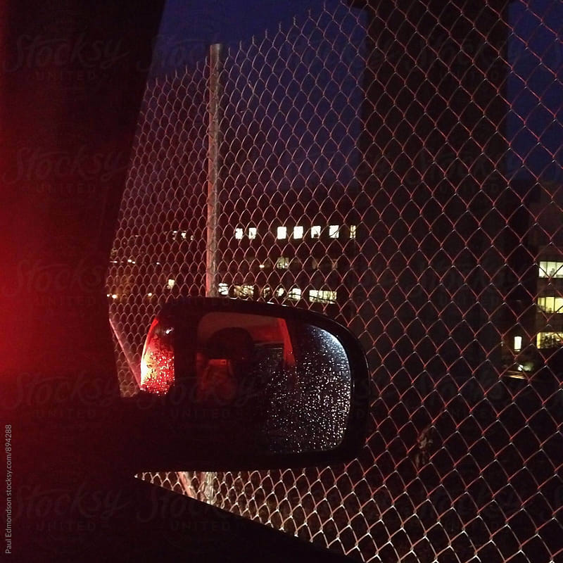 View of car door rearview mirror and chain-link fence at night by Paul Edmondson for Stocksy United