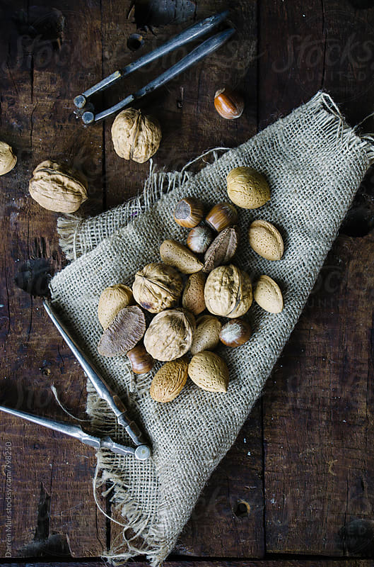 Mixed nuts and nutcrackers on burlap on wood background. by Darren Muir for Stocksy United