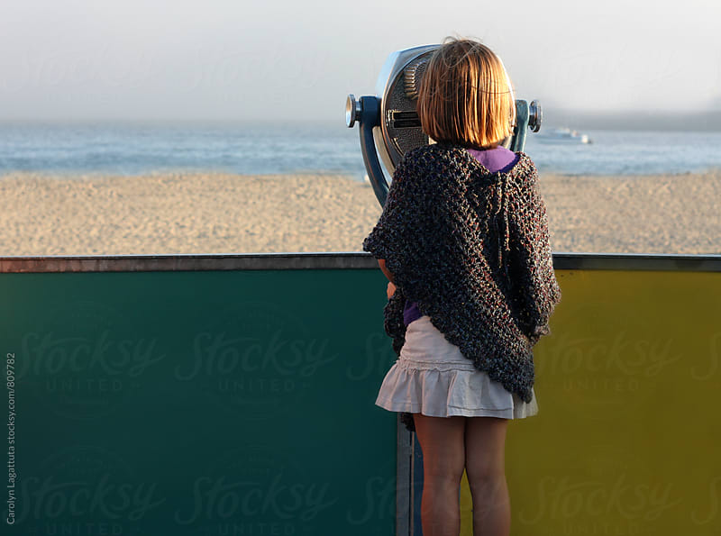 Little girl looking through a viewfinder toward the ocean by Carolyn Lagattuta for Stocksy United