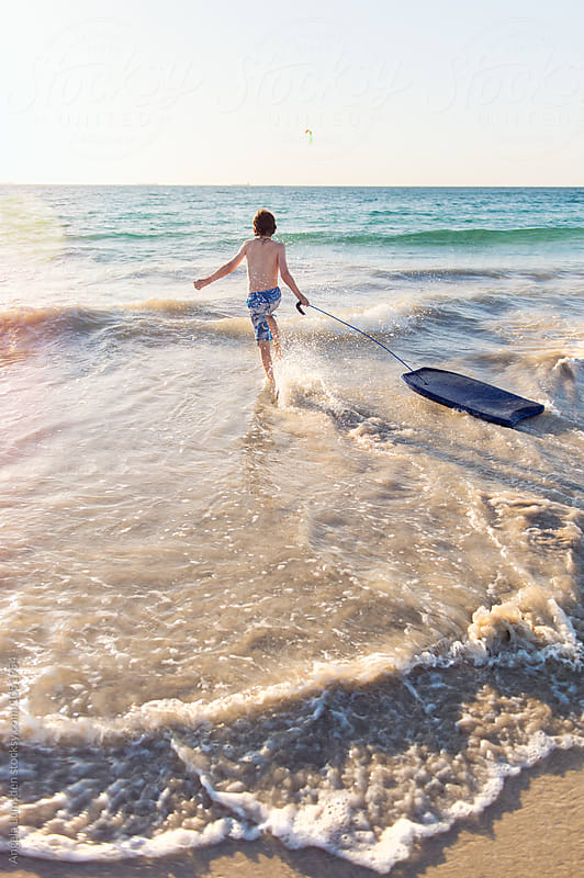 Boy running happily with a boogie board into the surf at the beach at sunset by Angela Lumsden for Stocksy United