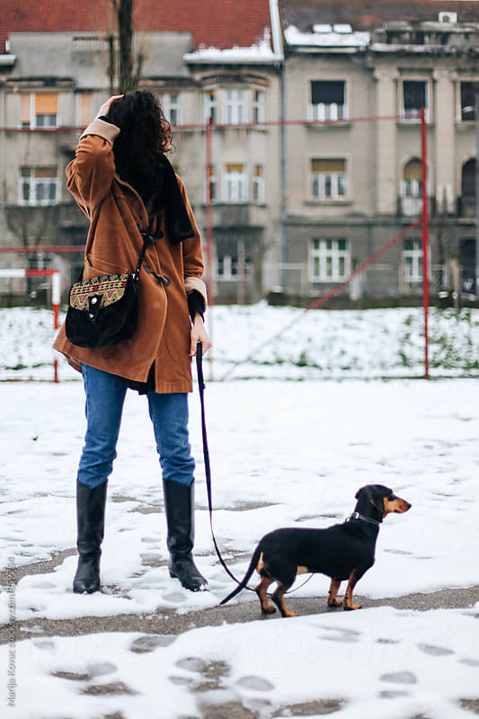 Stylish woman with her dog outdoor by Marija Kovac for Stocksy United