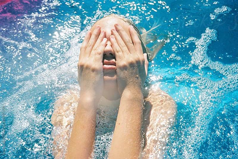 girl with hands on face in blue water with sparkles by wendy laurel for Stocksy United