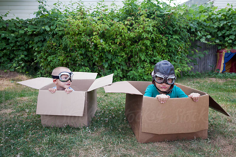 Brothers in aviator goggles racing cardboard boxes in the backyard by Carleton Photography for Stocksy United