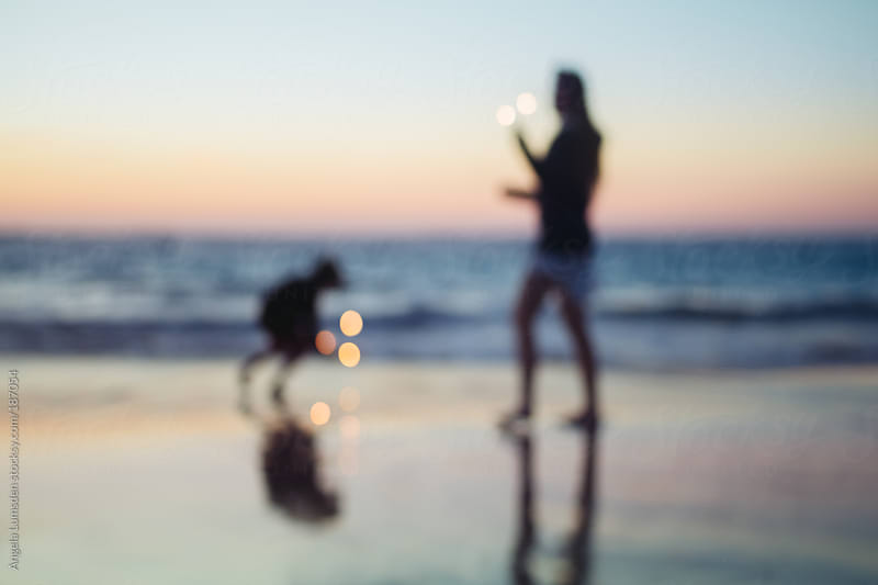 Children dancing with sparklers at the beach after sundown by Angela Lumsden for Stocksy United