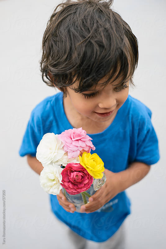 for you mommy: smiling boy holds a vase of flowers by Tara Romasanta for Stocksy United
