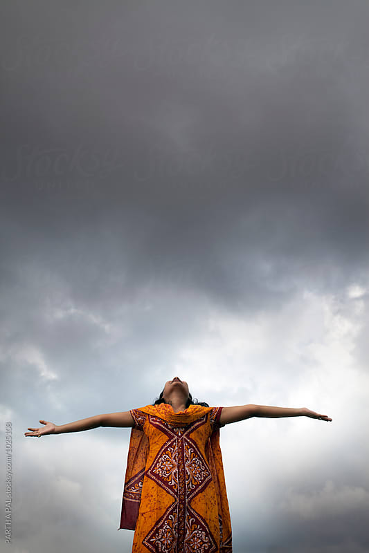 A young woman stretched arm and monsoon cloud at backdrop by PARTHA PAL for Stocksy United