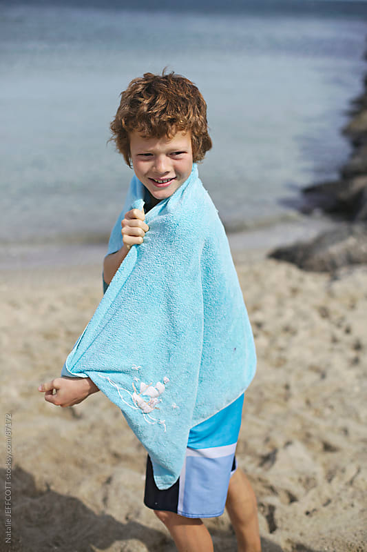 boy on beach by Natalie JEFFCOTT for Stocksy United