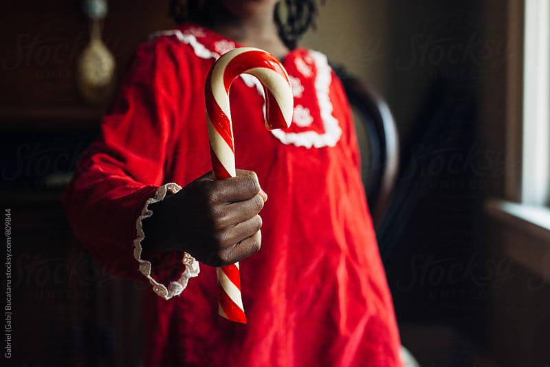 African American girl holding a candy cane by Gabriel (Gabi) Bucataru for Stocksy United