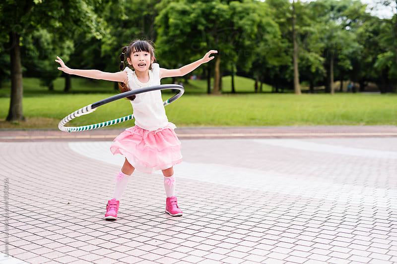 Girl exersicing with hula hoop outdoor by Lawren Lu for Stocksy United