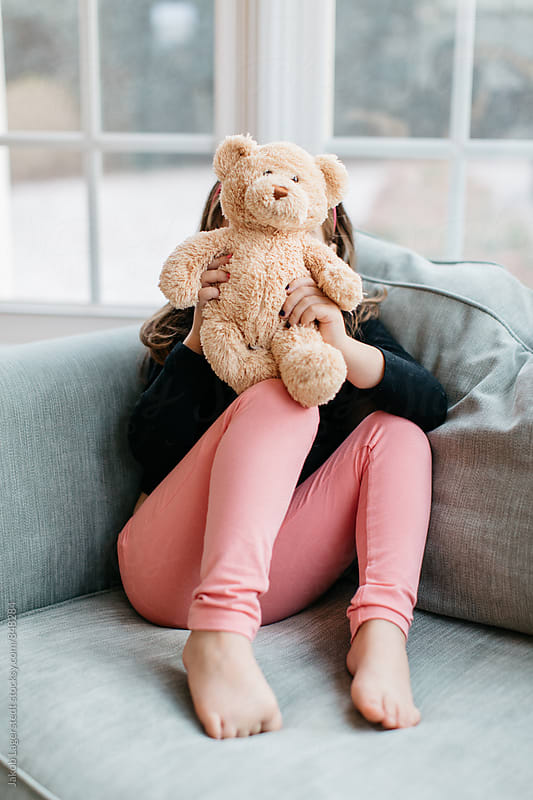 Cute young girl sitting on a big chair playing with her teddy bear  by Jakob for Stocksy United