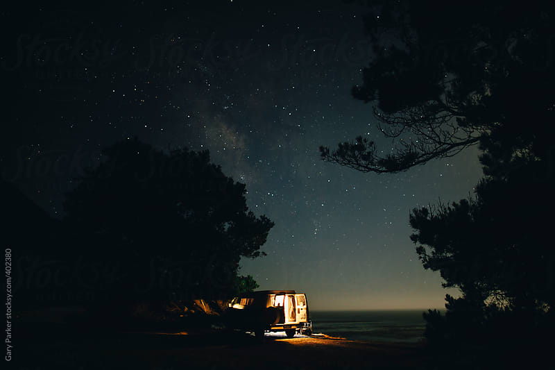 Van parked at the beach under the night stars
