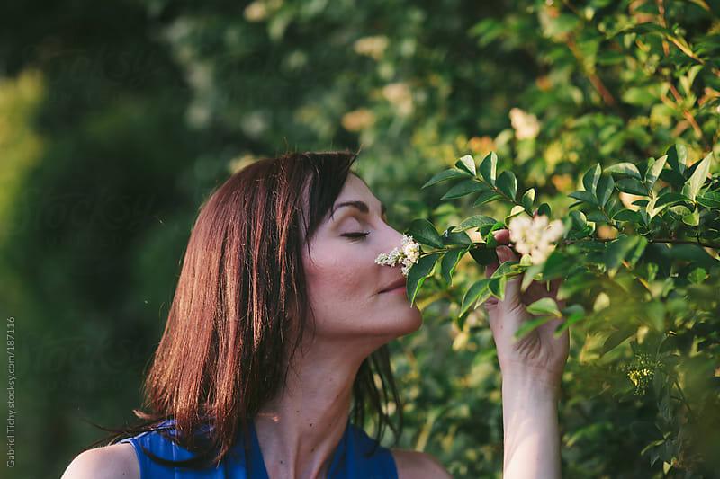 Pretty woman smelling a tree flower by Gabriel Tichy for Stocksy United
