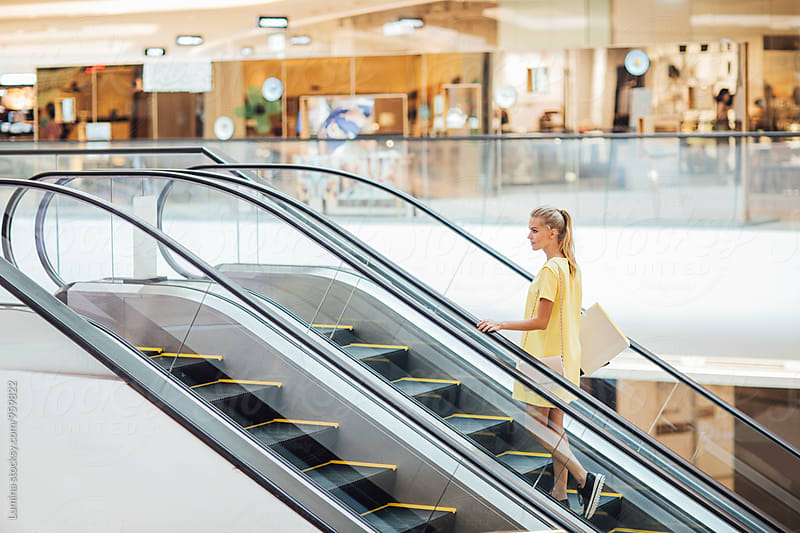 Caucasian Woman on an Escalator in the Shopping Mall by Lumina for Stocksy United