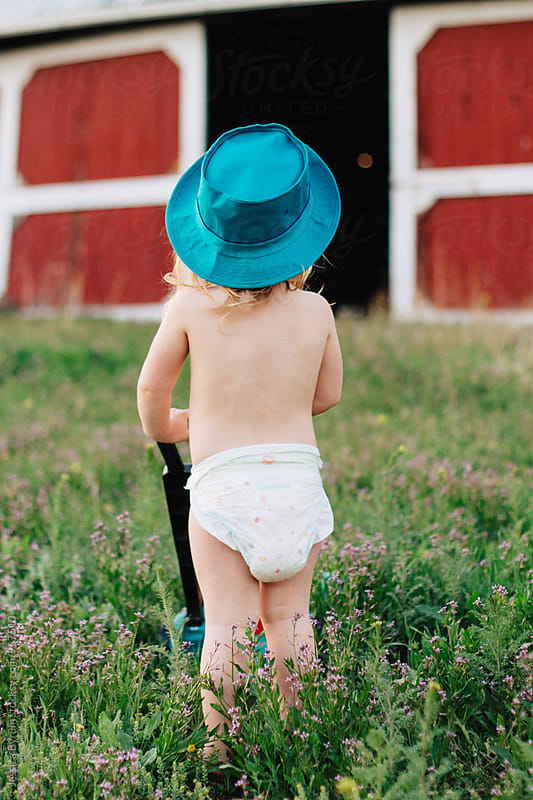 Toddler girl standing with toy lawn mower by Jessica Byrum for Stocksy United