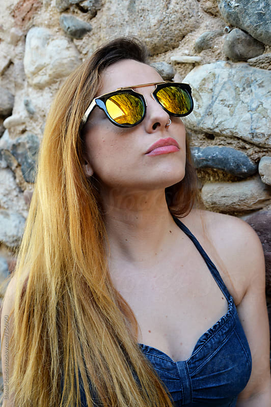 Portrait of a beautiful young woman with sunglasses by Bisual Studio for Stocksy United